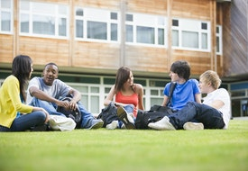 Five students sitting outdoors on lawn talking