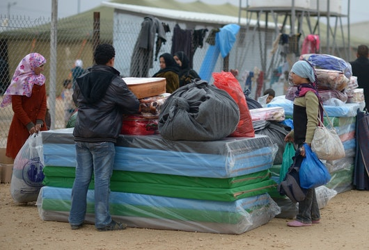 ZA'ATARI, JORDAN - FEBRUARY 01:  Refugees from Syria collect food and supplies from the UNHCR as they arrive at the Za'atari refugee camp on February 1, 2013 in Za'atari, Jordan. Record numbers of refugees are fleeing the violence and bombings in Syria to cross the borders to safety in northern Jordan and overwhelming the Za'atari camp. The Jordanian government are appealing for help with the influx of refugees as they struggle to cope with the sheer numbers arriving in the country.  (Photo by Jeff J Mitchell/Getty Images)