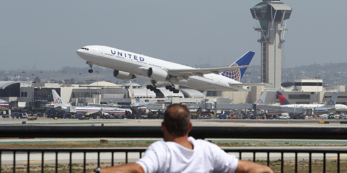 LOS ANGELES, CA - APRIL 22:  A United Airlines jet passes the air traffic control tower at Los Angles International Airport (LAX) during take-off on April 22, 2013 in Los Angeles, California. Delays have been reported throughout the nation because of the furloughing of air traffic controllers under sequestration. The average delay overnight in the Southern California Terminal Radius Approach Control (TRACON) was was three hours.  (Photo by David McNew/Getty Images)