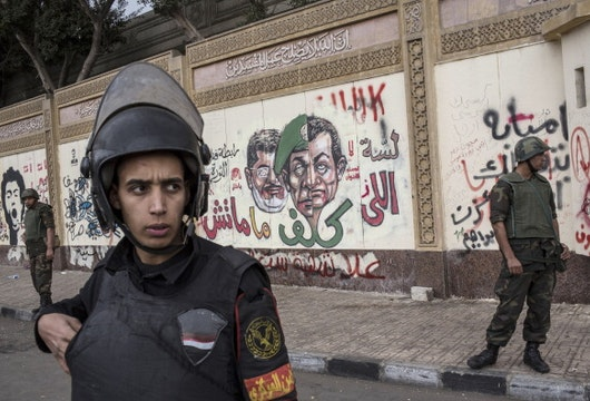 CAIRO, EGYPT - DECEMBER 14:  Soldiers stand guard in front of the presidential palace as anti-scaf graffiti is seen on the wall on December 14, 2012 in Cairo, Egypt. Opponents and supporters of Egyptian President Mohamed Morsi staged final rallies in Cairo ahead of tomorrow's referendum vote on the country's draft constitution that was rushed through parliament in an overnight session on November 29. The country's new draft constitution, passed by a constitutional assembly dominated by Islamists, will go to a referendum vote on December 15.  (Photo by Daniel Berehulak/Getty Images)