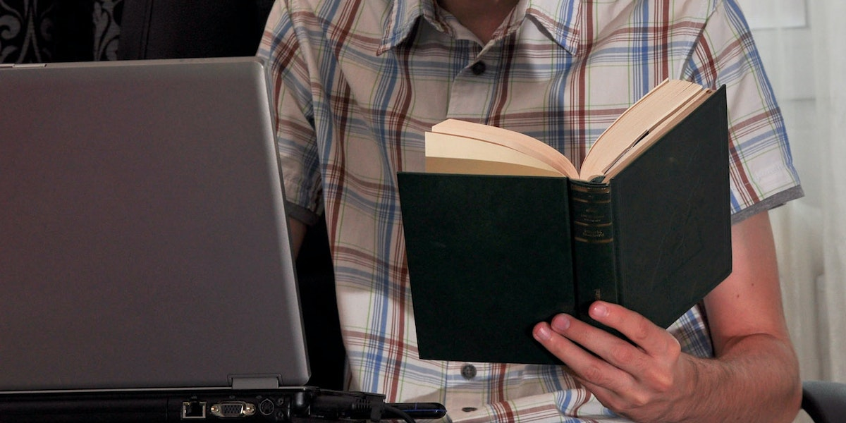 Student writing a paper from a book on a notebook computer