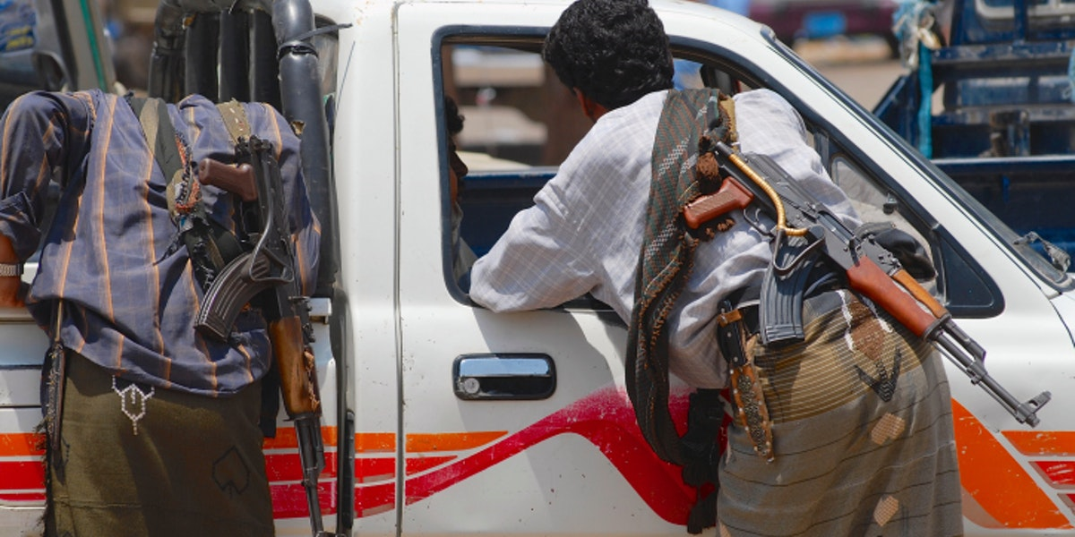 Yemeni people with Kalashnikov guns talk to a car driver.