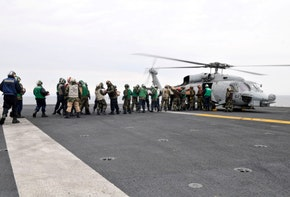 Sailors and Marines load supplies onto a HH-60H Seahawk.