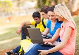 group of college students using laptop computers