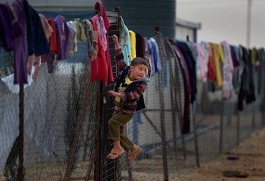 ZA'ATARI, JORDAN - FEBRUARY 01:  Young boy hangs on a fence with clothing hung from it, as Syrian refugees go about their daily business in the Za'atari refugee camp on February 1, 2013 in Za'atari, Jordan. Record numbers of refugees are fleeing the violence and bombings in Syria to cross the borders to safety in northern Jordan and overwhelming the Za'atari camp. The Jordanian government are appealing for help with the influx of refugees as they struggle to cope with the sheer numbers arriving in the country.  (Photo by Jeff J Mitchell/Getty Images)