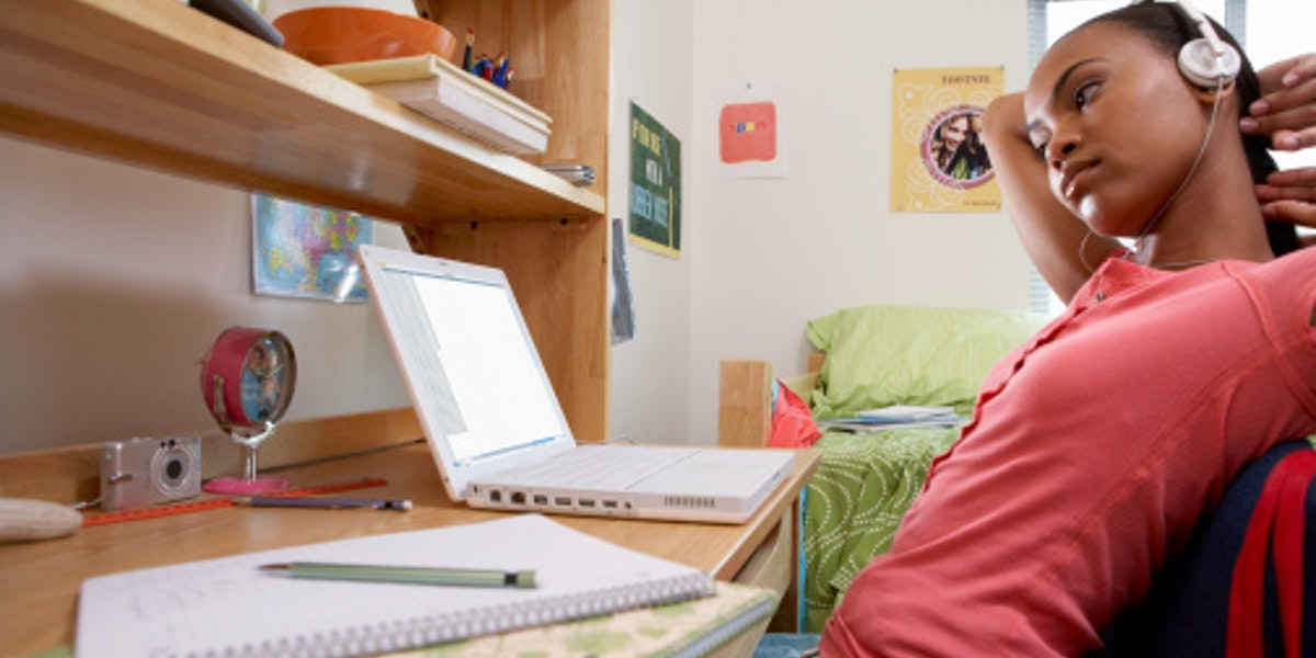 Young woman sitting at desk, using laptop, wearing headphones