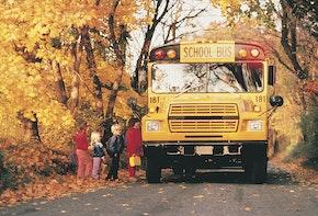 Children boarding school bus on rural road in autumn