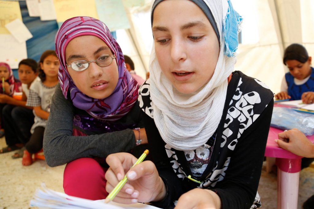Alia and Basma* (right), both aged 12, tackle a maths question at a temporary school in northern Lebanon, set up by UNICEF and Lebanese NGO Beyond Association with the help of UK aid. Source: Flickr, Russell Watkins/Department for International Development.