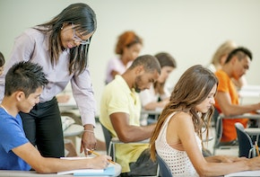 A multi-ethnic group of college age students are sitting in class and are working on an assignment.