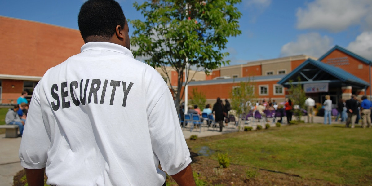 Security guard at a public junior high school -- students OOF in background