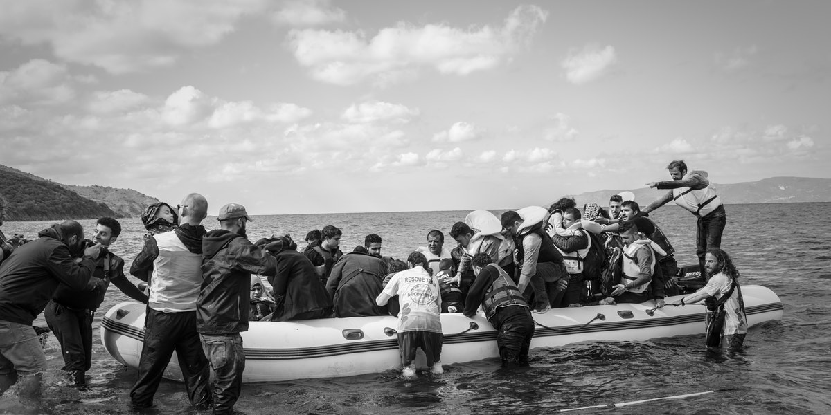 Lesbos, Greece - October 25, 2015: Volunteer lifeguards and others assist migrants out of their boat after landing on the Greek island of Lesbos, near the town of Skala Sikamineas. A photographer (left) photgraphs the landing. The coastline of Turkey is visible on the rightside of the photo.