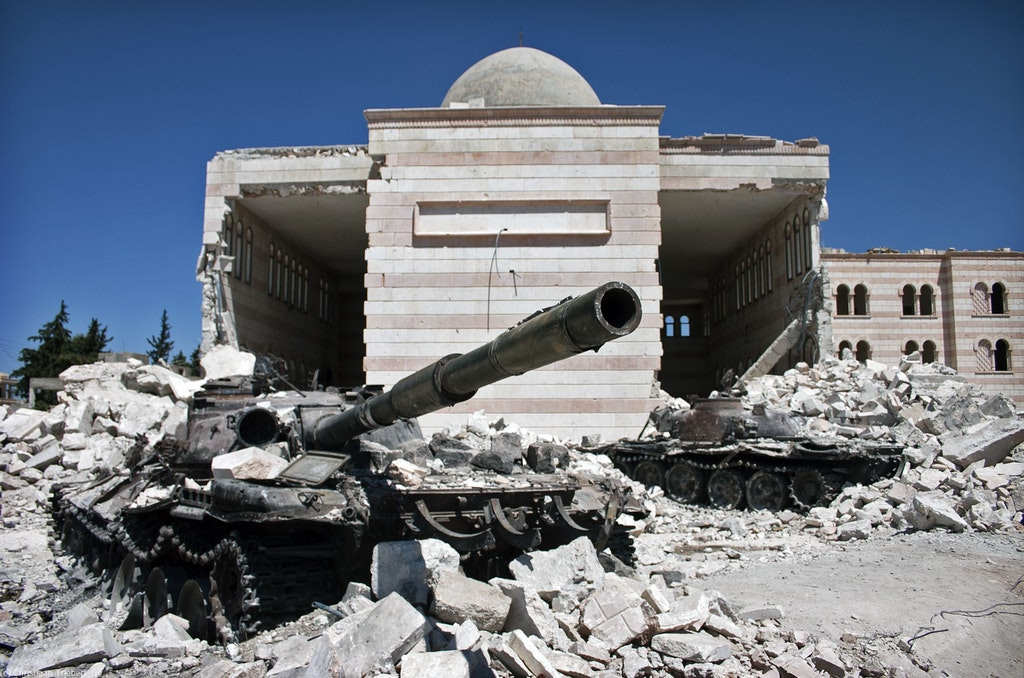Two destroyed tanks in front of a mosque in Azaz, Syria. A battle between the Free Syrian Army (FSA) and the Syrian Arab Army (SAA) was fought for control over the city of Azaz, north of Aleppo, during the Syrian civil war. Source: Christiaan Triebert.