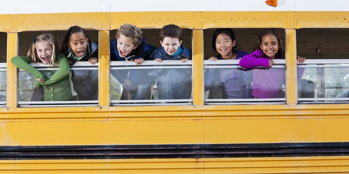 Multi-ethnic elementary school students (5 to 9 years) in school bus, looking out windows.