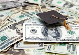 mini graduation cap on US money -- education costs