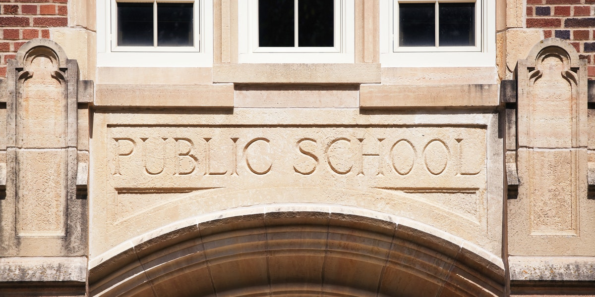 A Public School sign carved in granite about the entrance to an old high school.