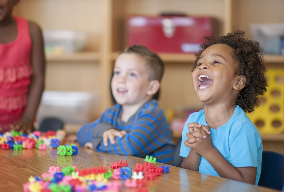 A multi-ethnic group of elementary age children are playing with toy blocks together at a table.