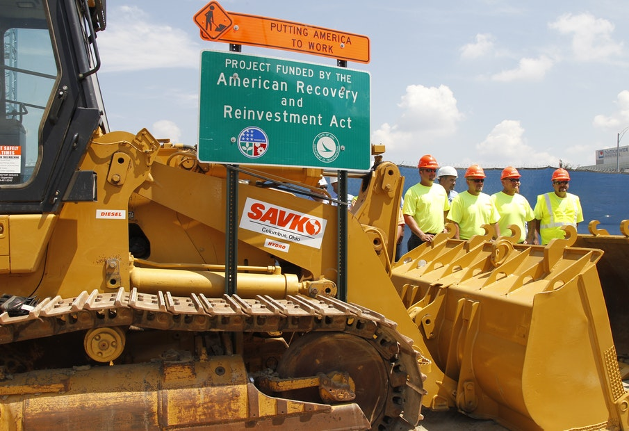 Construction workers look on before the arrival President Barack Obama at a highway road project funded by the American Recovery and Reinvestment Act in Columbus, Ohio, Friday, June 18, 2010. (AP Photo/Charles Dharapak)