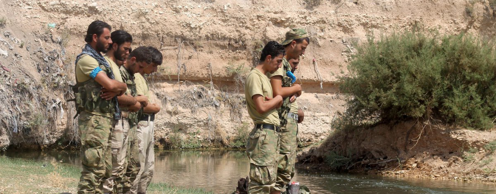Nour al-Din al-Zinki fighters pray on the banks of the Sajour River after expelling the U.S.-backed Syrian Democratic Forces. Nour al-Din al-Zinki was among the factions in contact with the U.S. State Department during ceasefire negotiations. Source: