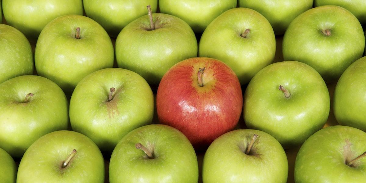 Red apple among green
