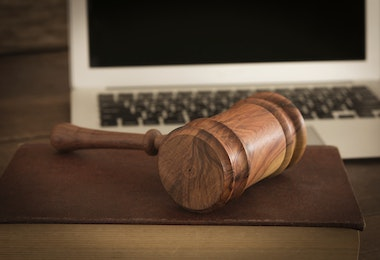 Wooden judge gavel on law book with laptop computer in background. Concept of cyber law or law about internet.