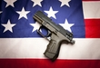 A concept image of liberty showing a pistol  on the American flag,