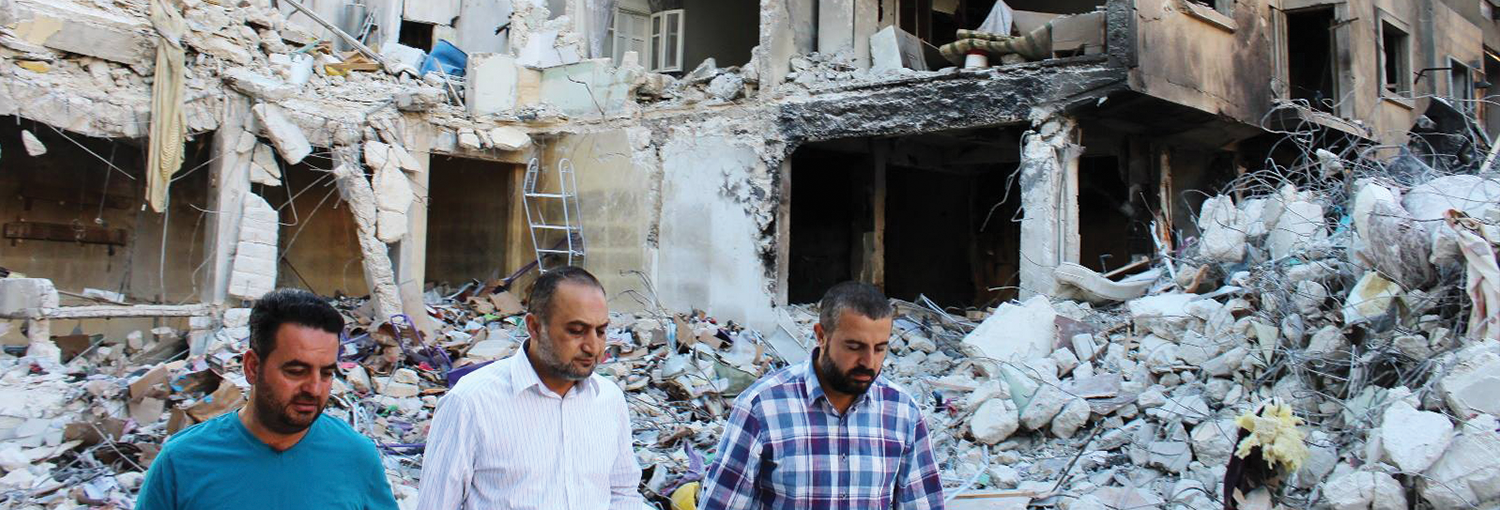 Provincial Council head Ghassan Hammou (left) visits scene of regime bombing in Idlib city.