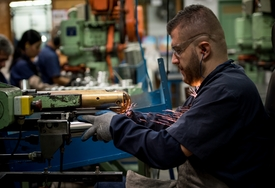 Latin American man working at a factory cutting metal