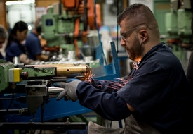 Latin American man working at a factory cutting metal