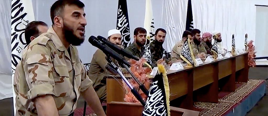 Zahran Alloush speaking at the declaration of the Unified Military Command in August 2014. Seated, left to right: Khaled Tafour, Abu Hamza al-Ghoutani, Yasser al-Qadri, Abdel-Nasr Shmeir, Abu Suleiman al-Zabadani, Samir Kaakeh, Said Darwish. Source: Rebel video.