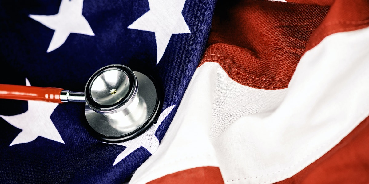 Red stethoscope on top of an American flag
