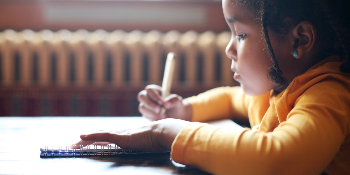 Profile of little African girl writing  in classroom.