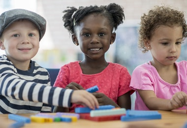 A multi-ethnic group of preschoolers are learning how to count with toys blocks.