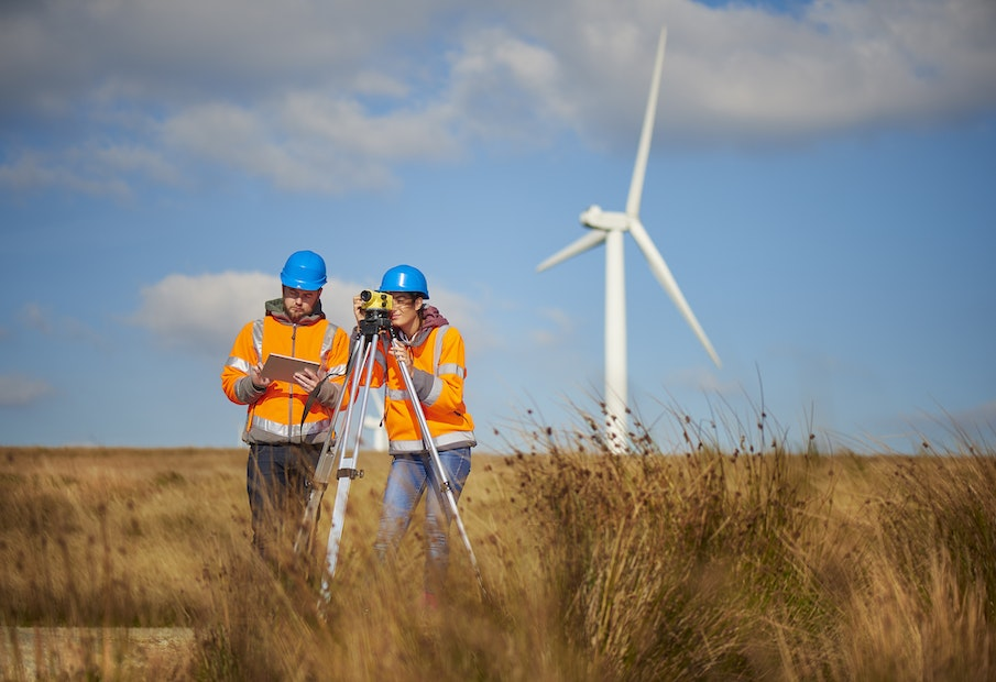 two wind farm engineers using a builder's level to plan out the expansion of the wind farm site. they are wearing orange hi vis jackets and blue hard hats . one is male , one is female. In the background wind turbines can be seen across the landscape.