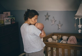 A happy new mother kisses her newborn baby on the cheek as she gets ready to put her down in the cot to sleep. The bedroom has stars on the walls and there are soft toys in the cot.