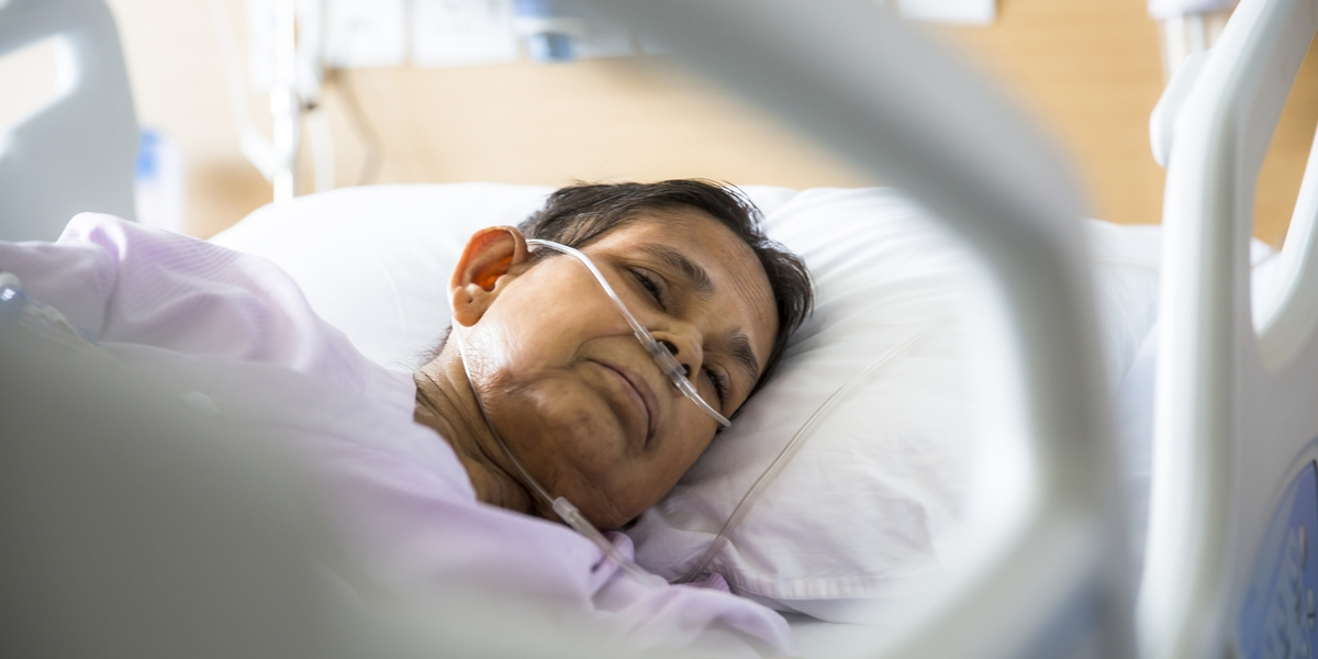 Old woman patient lying on Hospital bed with Oxygen tubes in her nose. She has her eyes closed.