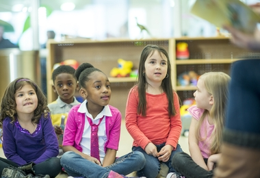 A multi-ethnic group of elementary age children are listening to their teacher read them a book in the library.