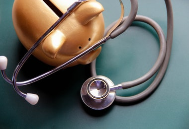 Piggy bank with Doctor's stethoscope on green wooden board. This photo may use as financial background.