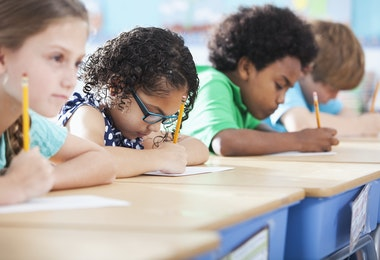 Multi-ethnic elementary school children writing in classroom.  Focus on Hispanic girl wearing eyeglasses (8-9 years).