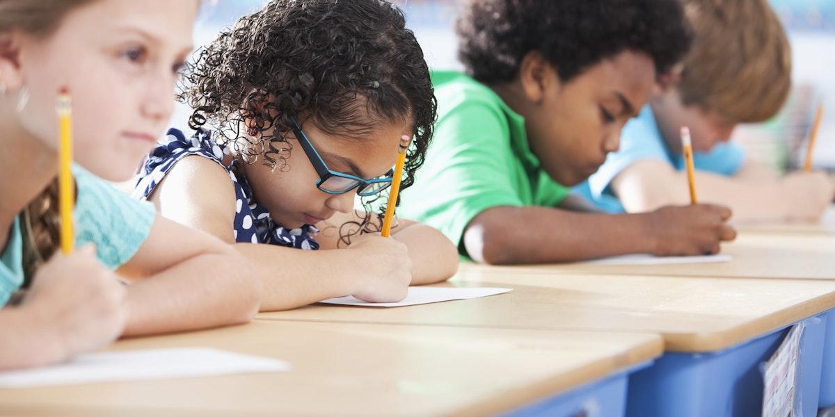 Multi-ethnic elementary school children writing in classroom.  Focus on Hispanic girl wearing eyeglasses (8-9 years).