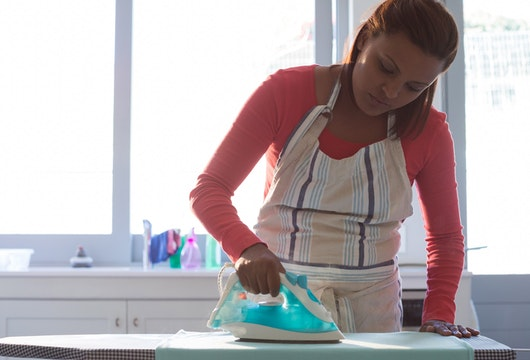 Woman ironing shirt on ironing board in kitchen at home
