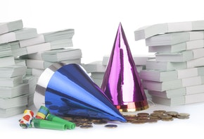 Stack of money with party horn blower and little hats isolated on white
