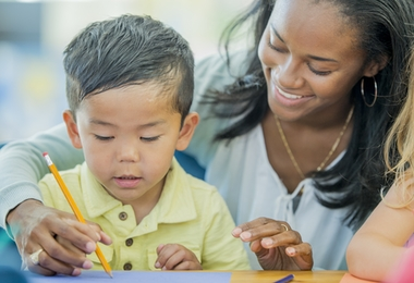 A teacher is helping a preschool students learn how to use his pencil.