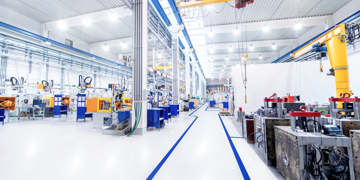 Horizontal image of huge new modern factory with robots and machines producing industrial plastic pieces and equipment. Wide angle view of futuristic machines and long aisle.