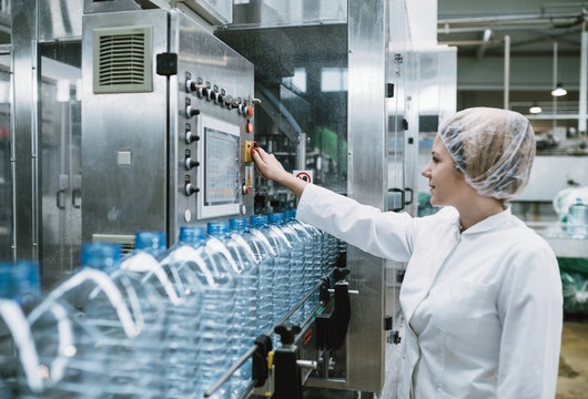 Young happy woman worker checking robotic line for bottling and packaging pure drinking water into bottles and canisters.