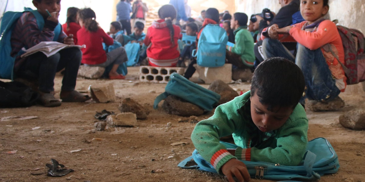 """On 13 November 2016, children lie or sit on the ground writing in notebooks at a make-shift school in rural Dar'a in the Syrian Arab Republic. Despite the ongoing violence across the country, children and dedicated teachers are doing all they can to keep their education going. Some 1.7 million children are currently (Nov 2016) out of school in the Syrian Arab Republic. Schools across the Syrian Arab Republic continue to be destroyed and damaged. This year (2016) 84 attacks on schools have resulted in the deaths of 69 children. UNICEF has provided 3.2 million children with learning materials, such as school bags, stationary and text books.  In November 2016, there is no safe place for children to learn or play in Syria. Underground facilities including basements and even caves, are used to shelter children from a war they grew up knowing nothing else. Displaced families from different areas in rural Damascus and Dar'a sought refuge in tents in rural Dar'a. The make-shift school receives up to 80 children on a daily basis. They are grouped according to age and knowledge in four groups, where each of the four former teachers, displaced themselves, teaches them reading and writing in both Arabic and English and the principals of mathematics. """"There is not a single space or even an extra tent that we could've used as a learning space,"""" says [NAME CHANGED] Muhammad, a teacher in this school. """"So we had to clean this fodder collection centre and turn it to a school where almost 80 children come on a daily basis to learn reading and writing, both in Arabic and English, and the principals of mathematics,"""" Muhammad continues.  The children are divided into four groups based on their knowledge and age. Each group is taught by one of the four former teachers, two male and two female teachers. """"Children have to share notebooks because we severely lack the necessary education supplies. They rotate on using the only six desks available.""""  [NAME CHANGED] Mona, a"""
