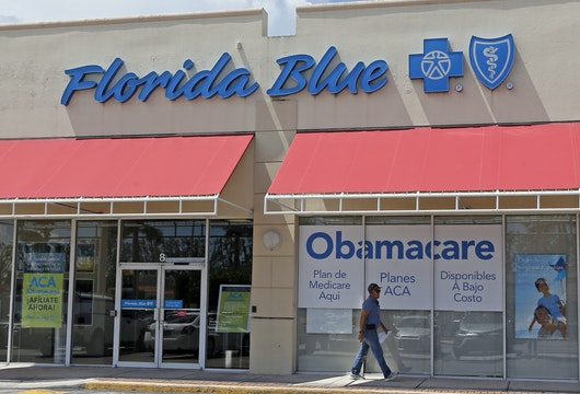 FILE - In this Thursday, July 27, 2017, file photo, a person walks by a health care insurance office in Hialeah, Fla. Health insurance shoppers will face a new deadline, rising prices and fewer options for help in many markets when the Affordable Care Act's main enrollment window for 2018 coverage opens Wednesday, Nov. 1. Insurance experts say those who need insurance should avoid waiting to do last-minute shopping. (AP Photo/Alan Diaz, File)