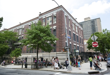 New York City, USA - June 17, 2013: Large school building in Brooklyn at the corner of Hicks Street and Middagh Street. Parents and nanny's pick up the kids after school.