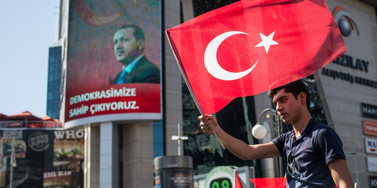 ANKARA, TURKEY - JULY 16: A man waves a Turkish flag from the roof of a car during a march around Kizilay Square in reaction to the attempted military coup on July 16, 2016 in Ankara, Turkey. Police regained control overnight after an attempted military coup against President Recep Tayyip Erdogan. The coup attempt claimed over 250 lives. President Erdogan urged his supporters to take to the streets in support to prevent any further flare ups.  (Photo by Chris McGrath/Getty Images)