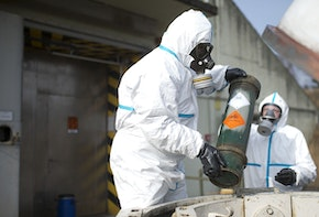 MUNSTER, GERMANY - MARCH 05:  Workers in protective clothing unload a dummy grenade during a press day at the GEKA facility on March 5, 2014 in Munster, Germany. GEKA is federally-funded and its sole function is the destruction of chemical weapons from military arsenals. Syria agreed to give up its chemical weapons last August and disposal, which is already underway on an American ship in the Mediterranean, is scheduled to be completed by June.  (Photo by Nigel Treblin/Getty Images)