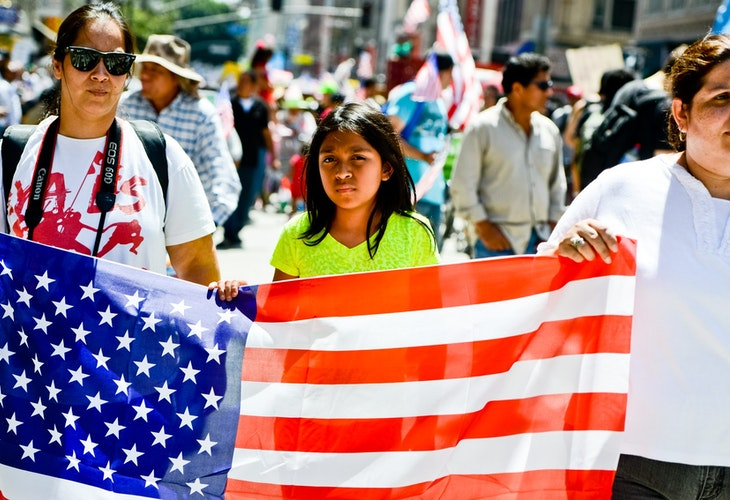 Los Angeles, USA - May 1, 2013: May Day March in Los Angeles Downtown, USA. People holding banners representing different social structures, organizations. March was mostly dedicated to Immigration reform discussed. Two women and teenager girl are holding big American flag.